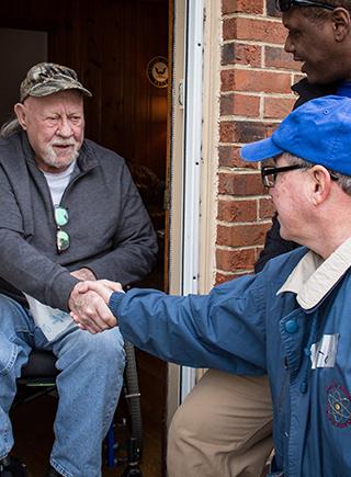 Veteran in wheel chair shaking hands with volunteer