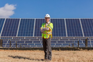 Employee in front of solar panels